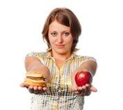La ragazza offre la mela e l'hamburger Immagine Stock