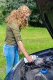 La ragazza olandese riempie il sistema di raffreddamento dell'automobile di liquido refrigerante immagine stock libera da diritti