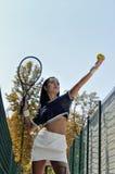 La ragazza oscilla la pallina da tennis della racchetta Immagine Stock