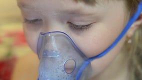 La ragazza in ospedale è curata con inalazione, bambino triste nella maschera di respirazione dell'ospedale per inalazione video d archivio