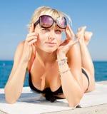 La ragazza osserva fuori da sotto gli occhiali da sole Fotografia Stock