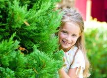 La ragazza osserva fuori dietro un albero Fotografia Stock Libera da Diritti