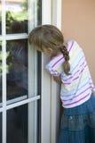 La ragazza osserva fuori la finestra Fotografia Stock Libera da Diritti