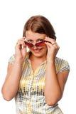 La ragazza osserva sopra gli occhiali Fotografia Stock