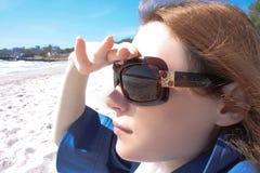 La ragazza osserva sul mare Immagine Stock