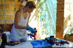 La ragazza ottiene il modello sulla pittura del tessuto in un'officina rurale Immagine Stock