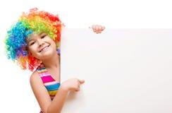 La ragazza in pagliaccio sta tenendo l'insegna in bianco Fotografie Stock