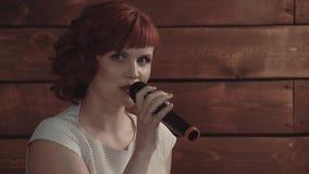 La ragazza parla nel microfono, contro un fondo dei bordi di legno, primo piano video d archivio