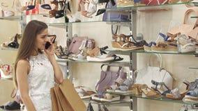 La ragazza parla sul telefono al negozio di scarpe fotografia stock