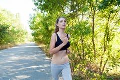 La ragazza passa gli sport pareggianti di un allenamento della foresta Fotografia Stock