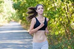 La ragazza passa gli sport pareggianti di un allenamento della foresta Immagine Stock