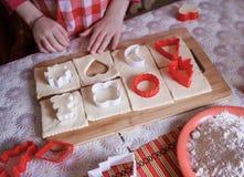 La ragazza passa la fabbricazione dei bisquits dalla pasta in cucina Immagini Stock Libere da Diritti