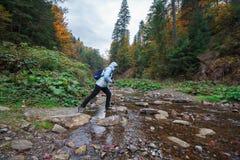 La ragazza passa la torrente montano delle rocce Immagine Stock