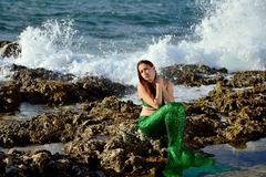 La ragazza pensierosa in una sirena che verde il costume si siede sulle rocce sulla spiaggia sui precedenti dell'acqua spruzza e  fotografia stock libera da diritti