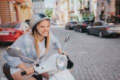 La ragazza persistente sta provando a funzionamento di inizio del motociclo È arrabbiata Può giro del ` t La ragazza indossa il c Immagine Stock Libera da Diritti