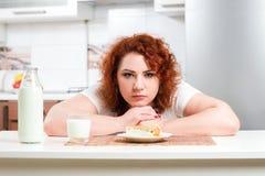 La ragazza più di dimensione avida mangia la torta dolce Il modello grasso affamato si siede da Th Fotografie Stock