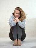 La ragazza piacevole si siede afferrando le mani delle ginocchia Immagine Stock