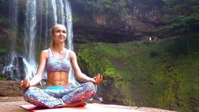 La ragazza piacevole si siede nella posa del loto dalla cascata che corre dalla scogliera video d archivio