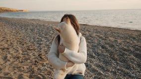 La ragazza piacevole in un maglione bianco abbraccia il suo cucciolo sveglio bianco di inu di shiba e lo mostra per amare sul mov stock footage