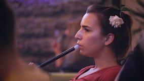 La ragazza piacevole in un night-club fuma un narghilé archivi video
