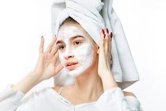 La ragazza piacevole in vestiti bianchi con un asciugamano bianco sui suoi capelli mette una maschera cosmetica sul suo fronte immagini stock libere da diritti