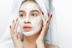 La ragazza piacevole in vestiti bianchi con un asciugamano bianco sui suoi capelli mette una maschera cosmetica sul suo fronte fotografia stock libera da diritti