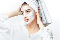 La ragazza piacevole in vestiti bianchi con un asciugamano bianco sui suoi capelli mette una maschera cosmetica sul suo fronte immagine stock libera da diritti