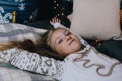 la ragazza in pigiama che allunga a letto dopo sveglia sulla mattina dell'inverno Immagini Stock Libere da Diritti