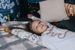 la ragazza in pigiama che allunga a letto dopo sveglia sulla mattina dell'inverno Fotografia Stock Libera da Diritti