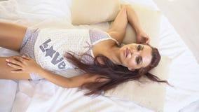 La ragazza in pigiami ha svegliato di mattina sta sedendosi su un letto stock footage