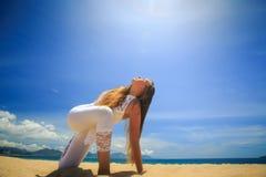 la ragazza in pizzo in asana di yoga ha girato l'angolo laterale sulla spiaggia Immagini Stock