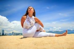 la ragazza in pizzo sulla spiaggia in asana di yoga ha intrecciato la parte posteriore di armi dietro Immagine Stock