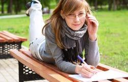 La ragazza pone su un banco e scrive Fotografia Stock