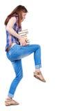 La ragazza porta un mucchio pesante dei libri Vista posteriore Fotografia Stock
