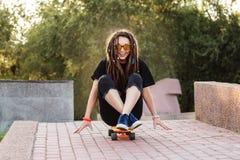 La ragazza positiva con i dreadlocks pattina su un longboard arancio su una sera dell'estate fotografie stock libere da diritti