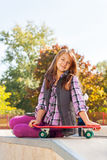 La ragazza positiva tiene il pattino si siede su terra Immagine Stock