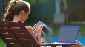 La ragazza pratica il surfing Internet sul telefono che si siede nella sedia dallo stagno stock footage