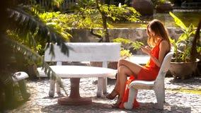La ragazza pratica il surfing Internet sul telefono in giardino pittorico archivi video