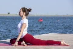 La ragazza pratica l'yoga sulla riva del lago, il concetto di godere della segretezza e della concentrazione, luce solare fotografia stock libera da diritti
