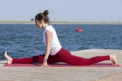 La ragazza pratica l'yoga sulla riva del lago, il concetto di godere della segretezza e della concentrazione, luce solare immagine stock