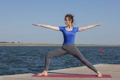 La ragazza pratica l'yoga sulla riva del lago, il concetto di godere della segretezza e della concentrazione, luce solare immagini stock libere da diritti