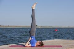 La ragazza pratica l'yoga sulla riva del lago, il concetto di godere della segretezza e della concentrazione, luce solare fotografie stock libere da diritti