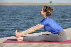 La ragazza pratica l'yoga sulla riva del lago, il concetto di godere della segretezza e della concentrazione, luce solare immagine stock libera da diritti