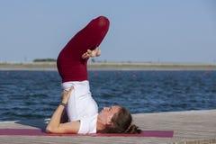 La ragazza pratica l'yoga sulla riva del lago, il concetto di godere della segretezza e della concentrazione, luce solare fotografia stock