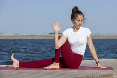 La ragazza pratica l'yoga sulla riva del lago, il concetto di godere della segretezza e della concentrazione, luce solare fotografie stock