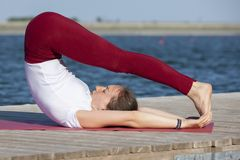 La ragazza pratica l'yoga sulla riva del lago, il concetto di godere della segretezza e della concentrazione, luce solare immagini stock