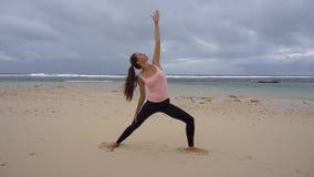 La ragazza pratica l'yoga vicino all'oceano video d archivio