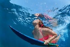 La ragazza praticante il surfing con il bordo si tuffa sotto l'onda di oceano immagine stock