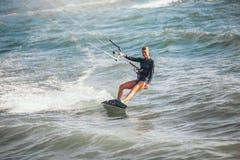 La ragazza praticante il surfing dell'aquilone in costume da bagno sexy con l'aquilone nella guida blu del mare ondeggia Immagini Stock Libere da Diritti