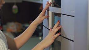 La ragazza preme i bottoni sul touch screen del forno moderno nella cucina stock footage